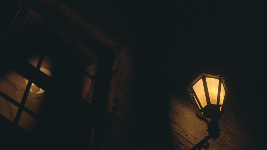 Scary haunted dark night in London alley way looking up at old street lamp and window through metal bars. Royalty-Free Stock Footage #1053961031