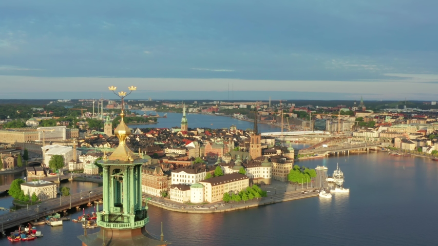 Stockholm City Hall drone shot on beautiful summer evening. Golden crowns close up and rooftop. Old town palace and city center in background. Sunset light over Stadshuset in Sweden capital Royalty-Free Stock Footage #1053961079