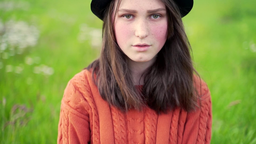Close up portrait of young attractive shy girl in black hat with freckles and rose cheeks wear red sweater. Teenager with brown hair looking at camera on green nature background alone with sad eyes.