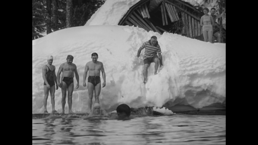 CIRCA 1939 - Men and women in Victorian swimwear walk through snowdrifts in a Mount Hood, Oregon forest and have a snowball fight.