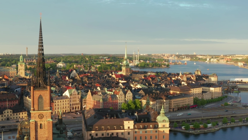 Stockholm old town drone shot on summer evening at sunset. Rooftops and old buildings from above. Riddarholm German church and ocean overview video. gamla stan city center in Sweden capital city Royalty-Free Stock Footage #1053961952