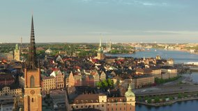 Stockholm old town drone shot on summer evening at sunset. Rooftops and old buildings from above. Riddarholm German church and ocean overview video. gamla stan city center in Sweden capital city