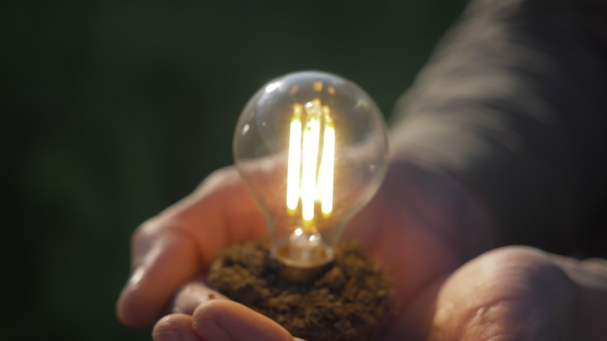 Idea solar energy in nature, hand holding light bulb. Eco energy saving, alternative solar energy, renewable resources, electricity. hand holding light bulb. innovation and inspiration | Shutterstock HD Video #1053962042
