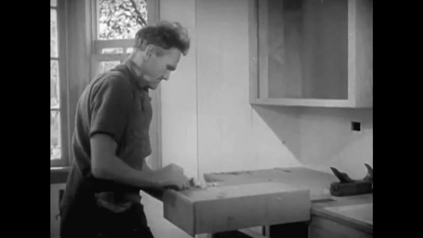 CIRCA 1940s - Carpenters install flooring, a door and cabinets, in 1940. | Shutterstock HD Video #1053966359