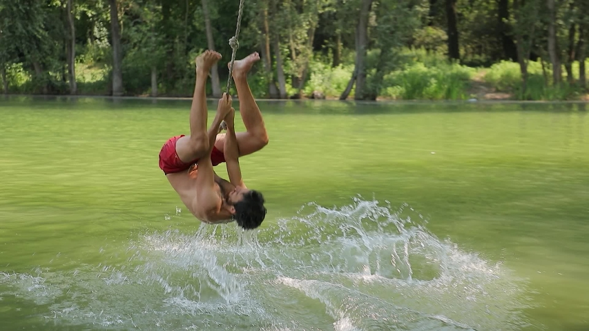 Guy jumping from rope swing hitting the water head down Royalty-Free Stock Footage #1053974483