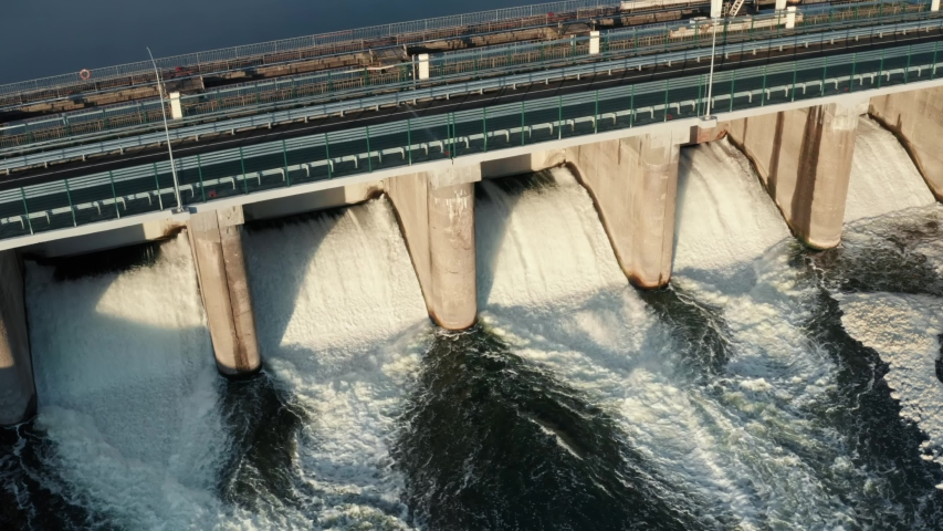 Hydroelectric dam with flowing water through gate, aerial view from drone