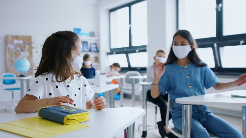 Children with face mask back at school after covid-19 quarantine and lockdown, greeting. Royalty-Free Stock Footage #1053984608