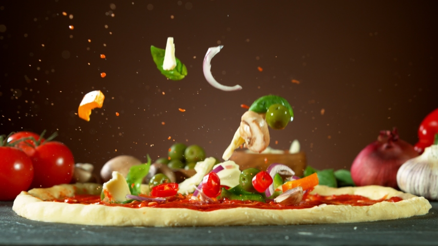 Super slow motion of falling pizza ingredients on yeast dough. Filmed on high speed cinema camera, 1000 fps.