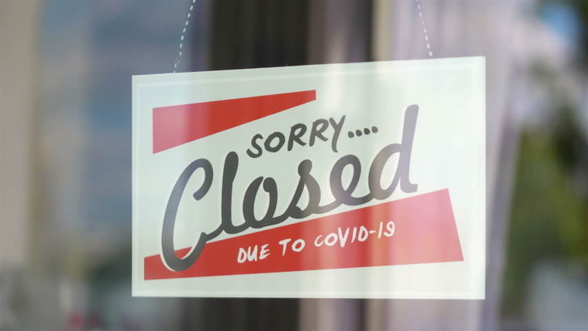 Closed sign hanging on the glass during pandemic time in 4K Slow motion 60fps | Shutterstock HD Video #1053990749