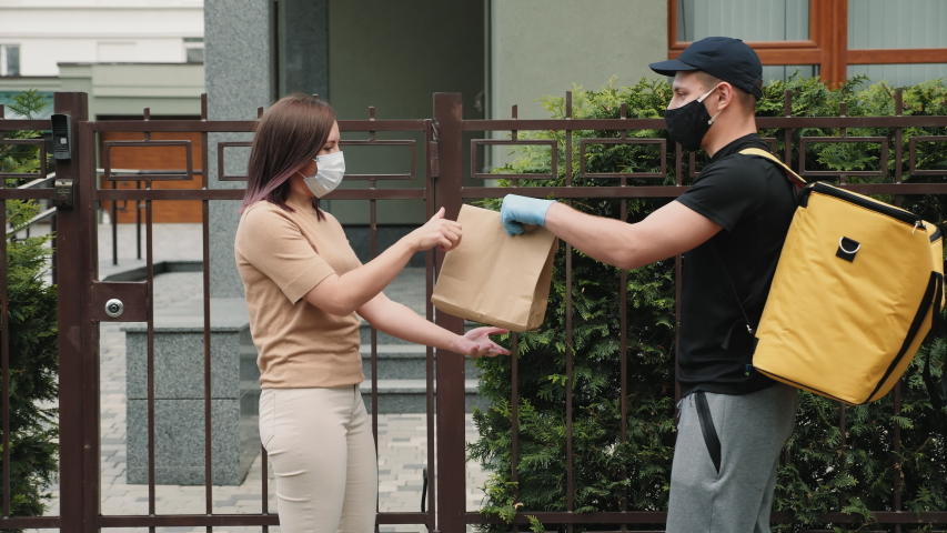 Courier wearing thermal backpack, mask, and gloves hands over a paper bag of food to a beautiful female customer near an office building. Middle shot Royalty-Free Stock Footage #1053992012