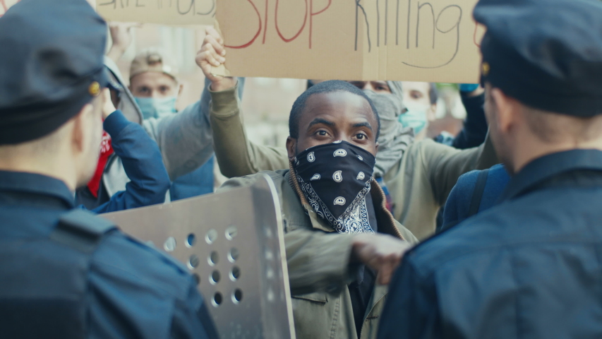 Young African American guy protester screaming and shouting at policemen at demonstration for human rights. USA protesters fighting and quarrelling with cops at protest against police violence. | Shutterstock HD Video #1053998507