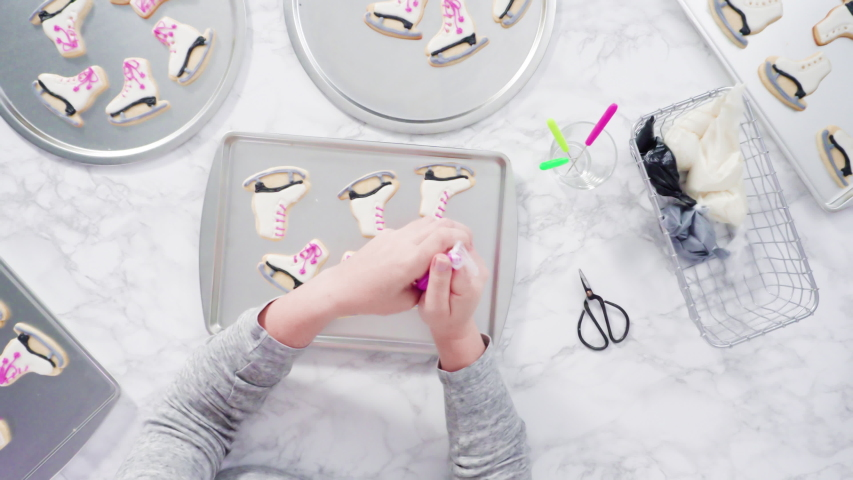 Flat lay. Icing figure skate shaped sugar cookies with royal icing. | Shutterstock HD Video #1053999269