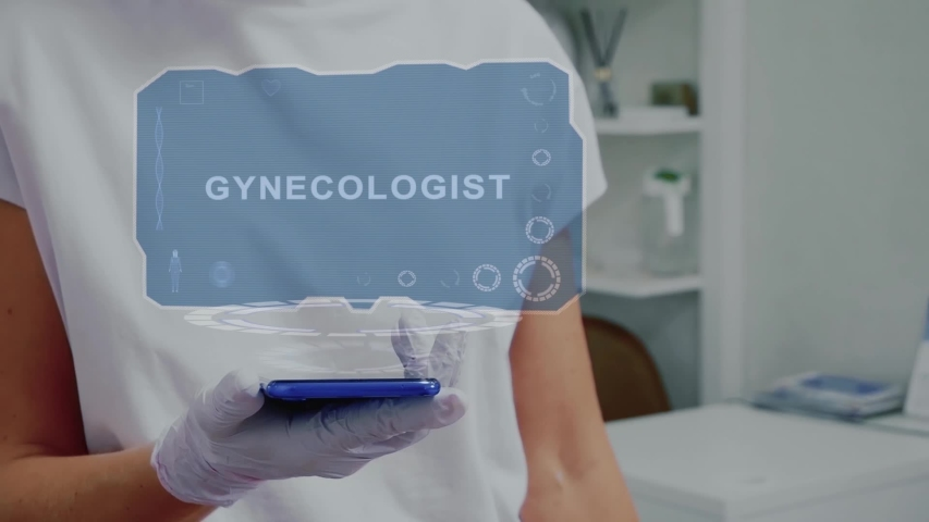 Doctor in medical glove against background of doctor's office with HUD hologram text Gynecologist. Hand holds futuristic holographic gadget. Medical technology concept of the future | Shutterstock HD Video #1054003994