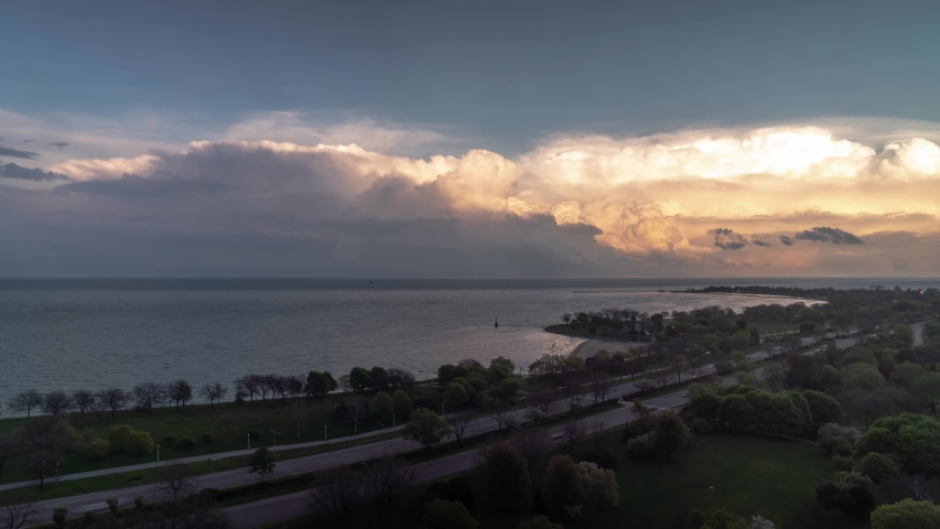 Aerial cloudscape cloudy sky timelapse over the water of Lake Michigan and Lake Shore Drive in Chicago on a blue sky day at sunset as clouds begin to change to pink and orange colors.