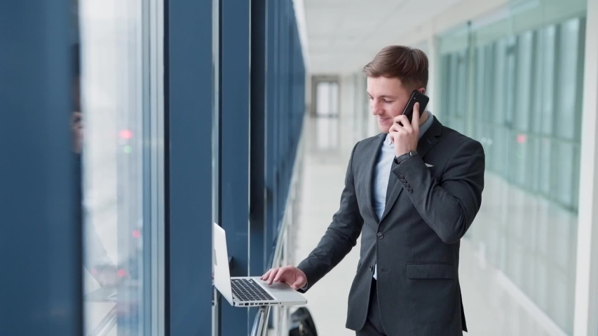 Stylish young man talking on the phone and working on a laptop | Shutterstock HD Video #1054012646