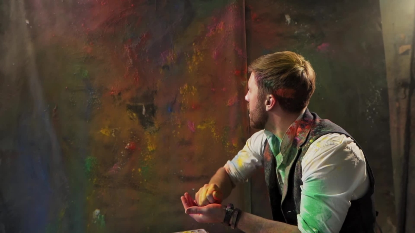 Artist throws colored dry paint on the canvas | Shutterstock HD Video #1054013993