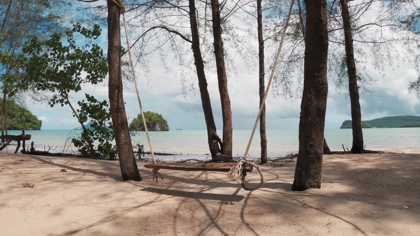 Empty swing rocking on the sea, in trees, on the sandy beach.