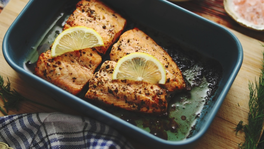 Roasted salmon in heat proof dish. With aromatic dill, lemon, salt and pepper on sides. Top View. Flat lay