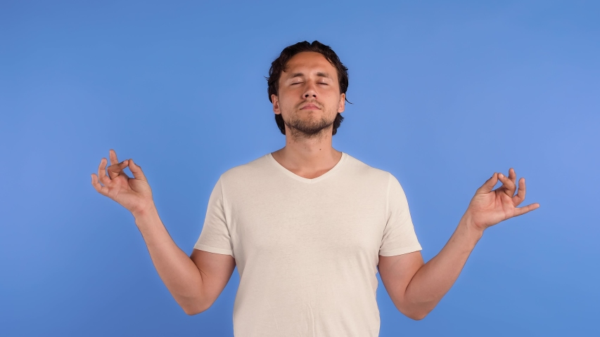Bearded fellow in white t-shirt. He is looking tired, showing gyan mudra hands gesture, meditating while posing on blue studio background. Close up | Shutterstock HD Video #1054022522