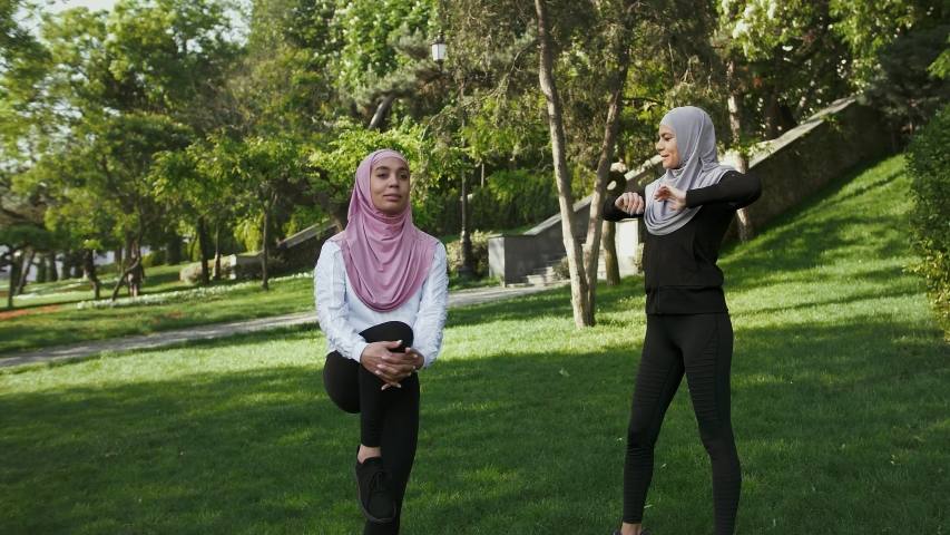 Two dark-skinned muslim women in sportswear and colorful hijabs. They smiling and talking, doing exercises standing on green grass of landscaped park