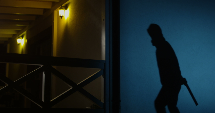 Burglar Intruding in the House from Backyard at Night Casting a Shadow and Jumping over Fence Breaking in with a Weapon and Flashlight Shot on Red Epic