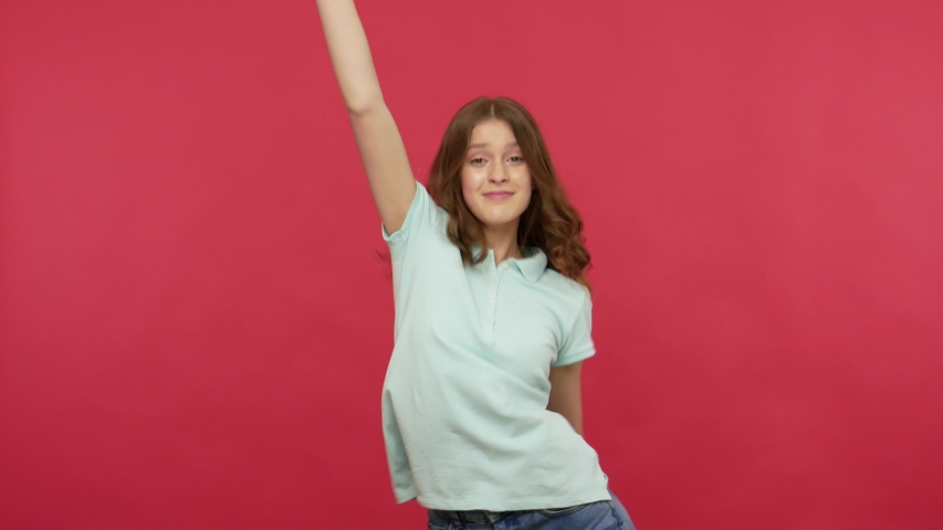 Extremely happy young woman in t-shirt dancing joyfully and celebrating success, enjoying energetic music, moving in dynamic winning dance, quick rhythm. indoor studio shot isolated on red background Royalty-Free Stock Footage #1054031726