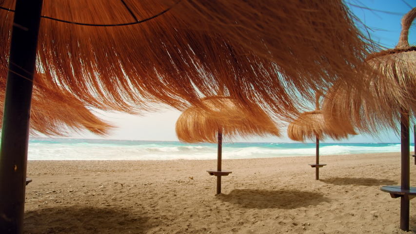 Cinematic beautiful view on palm umbrellas at expensive luxurious resort or holiday destination. Amazing vacation location for romantic getaway or weekend spa retreat. Empty paradise beach, cancelled Royalty-Free Stock Footage #1054031981
