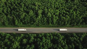 Two Semi Trucks with white trailer and cab driving / traveling alone on dense flat forest asphalt straight road, highway perspective follow vehicle aerial mid shot at sunset / Freeway trucks traffic