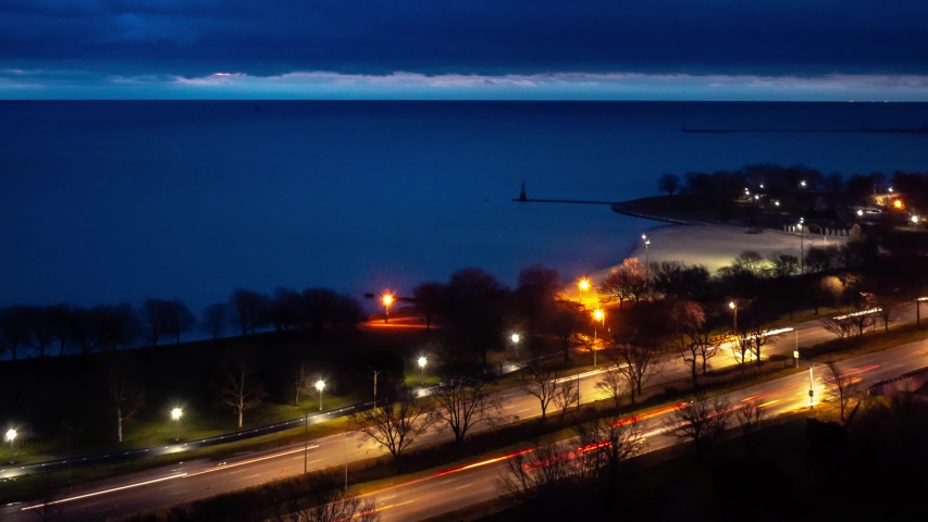 Beautiful zoom out aerial night time lapse of traffic and light trails on Lake Shore Drive in Chicago as heavy cloud cover moves over the calm water of Lake Michigan.