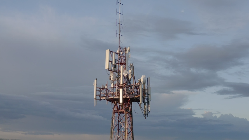 Cellular and Internet tower with antennas and Dish Tv for transmitting 3G, 4G or 5G signals, aerial shot. | Shutterstock HD Video #1054036769