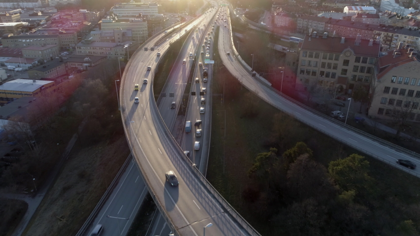 Aerial view of elevated highway traffic at sunset. Drone shot flying over junction, rush hour cars driving by. Urban transportation and air pollution background in 4K resolution Royalty-Free Stock Footage #1054037954