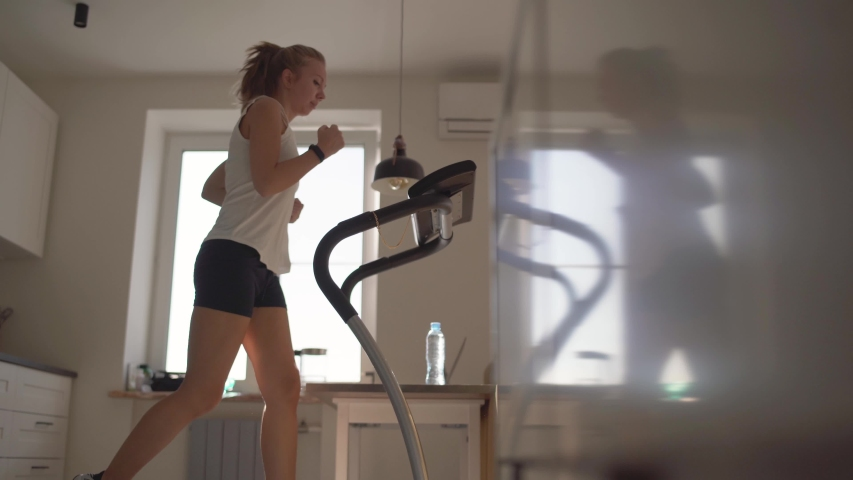 Woman running on running machine at home.Full length profile shot of a fit woman jogging on a treadmill in the kitchen. | Shutterstock HD Video #1054040960