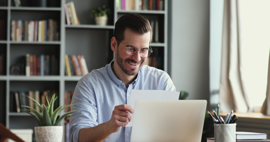 Curious smiling young man in glasses opening paper envelope, reading letter with good news. Happy handsome businessman received investment notification or banking loan approval or salary bonus. | Shutterstock HD Video #1054044065