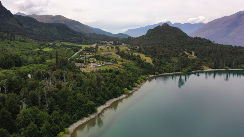 Aerial panning shot of trees at lakeshore near mountain range, drone flying forward over lake against sky - Queenstown, New Zealand | Shutterstock HD Video #1054049330