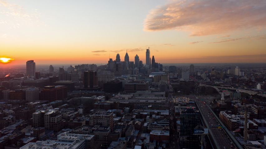 Aerial time lapse of Philadelphia skyline during colorful, orange sunset with large, modern skyscrapers, neighborhoods, and cars driving along the road