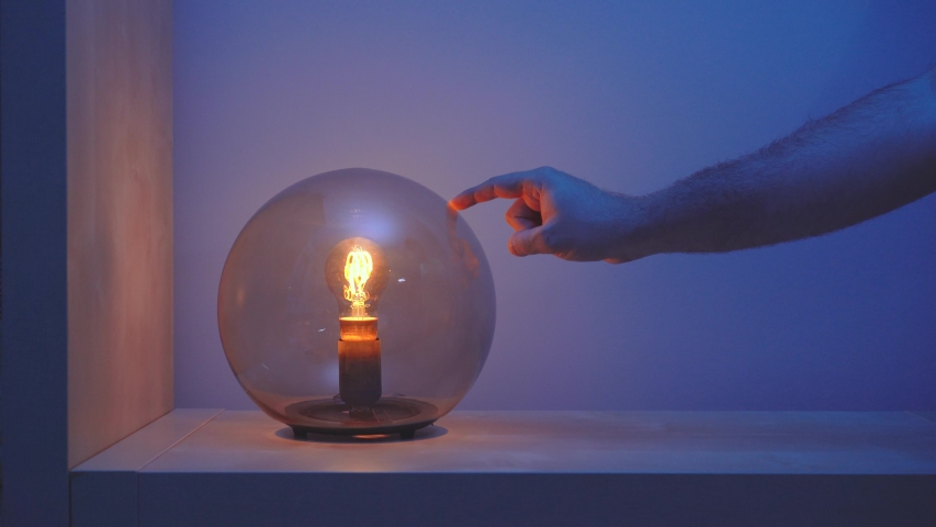 Faceless person turning on and after few seconds turning off with her finger creative table lamp with dark glass dome on in blue room in evening