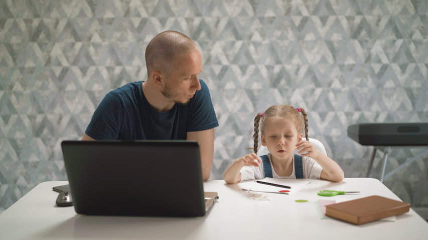 Young father helps pretty little daughter to unglue sticker from paper sitting at white table with modern laptop in brightly lit room at isolation | Shutterstock HD Video #1054054751