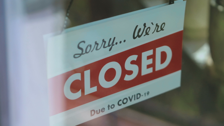 Closed sign hang on the glass in pandemic time in 4K Slow motion 60fps | Shutterstock HD Video #1054058552