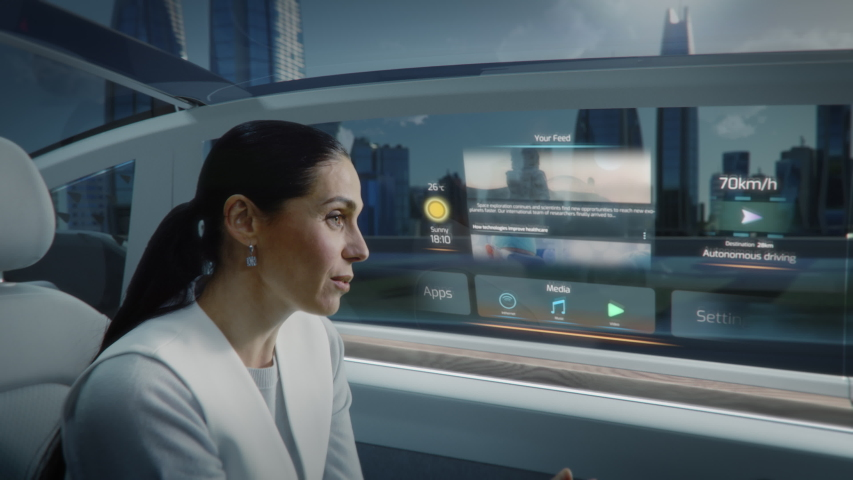 Futuristic Concept: Zoom Out View of an Attractive Female Reading the News on a Futuristic Augmented Reality Interface while Talking to Another Passenger. Riding in an Autonomous Self-Driving Car.