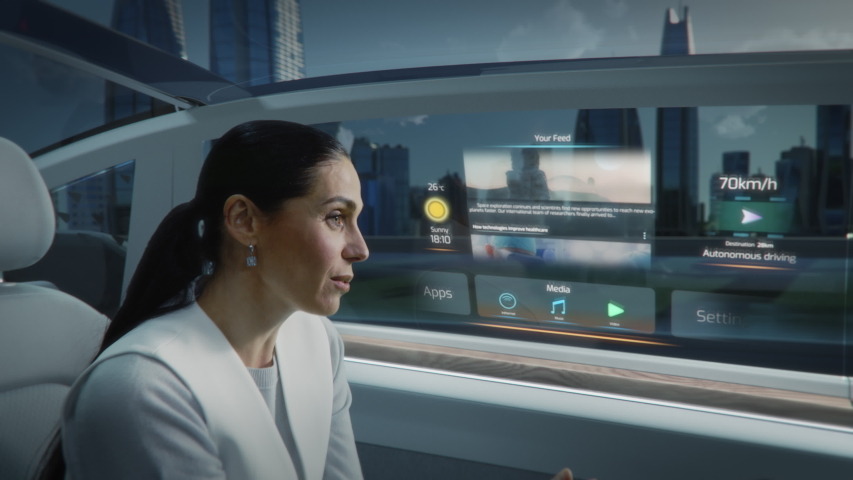 Futuristic Concept: Zoom Out View of an Attractive Female Reading the News on a Futuristic Augmented Reality Interface while Talking to Another Passenger. Riding in an Autonomous Self-Driving Car | Shutterstock HD Video #1054062338