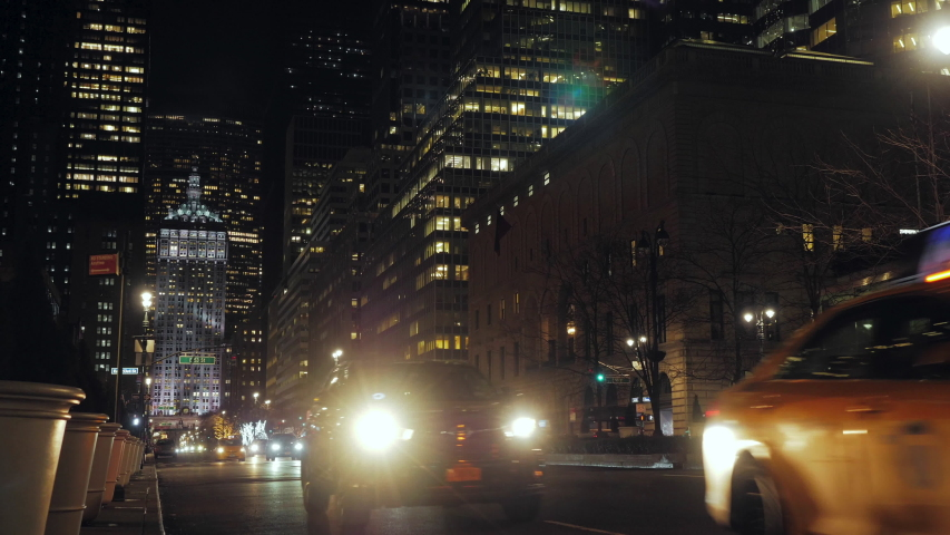Night view of a New York street surrounded by illuminated skyscrapers crossed by cars and taxis going towards the camera. a car headlight illuminates the camera creating a flare. red traffic lights