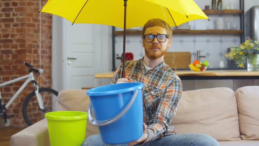 Portrait of upset young hipster guy in glasses sitting on couch at home under umbrella holding plastic bucket collecting water falling from ceiling Royalty-Free Stock Footage #1054065872