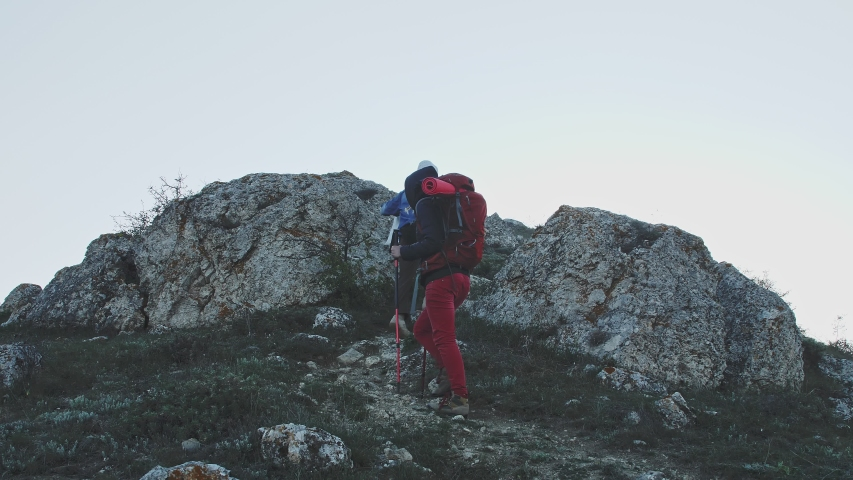 A man and a woman with backpacks climb into the mountains view from below and from the back | Shutterstock HD Video #1054067438