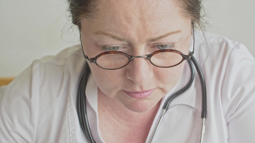 The face of a female doctor she is focused on work Light tension manifests on the face The idea of a learning process or problem-solving by specialists | Shutterstock HD Video #1054067462