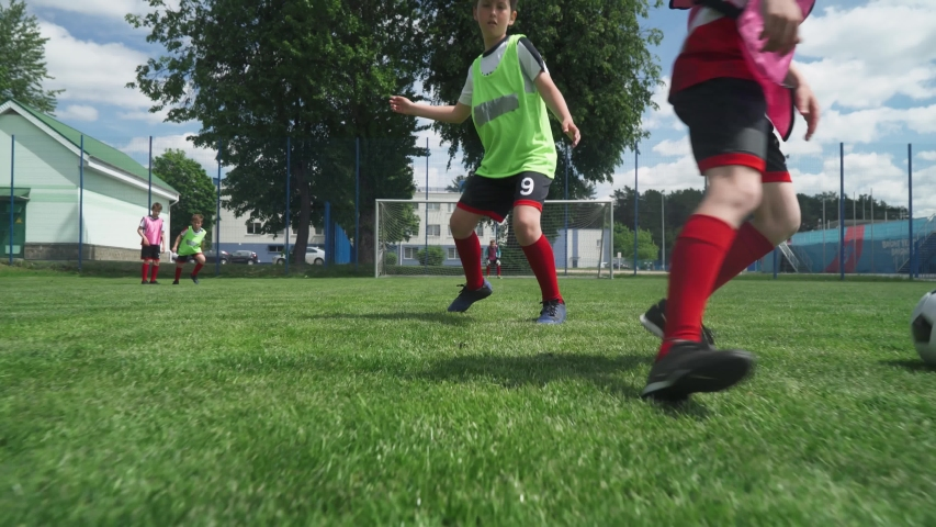 Group of young boys play soccer, training day on the football field, teenagers play football on a summer day, boy scores a goal.