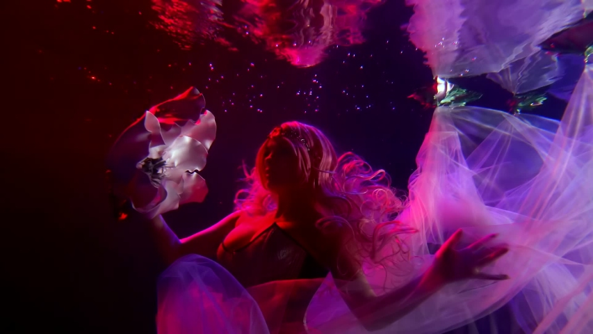 A girl Princess with a crown is under water, she is illuminated by pink lighting, her train dress and hair are flying under the water. She makes and smooth movements, in her hands she has a flower Bud | Shutterstock HD Video #1054068713