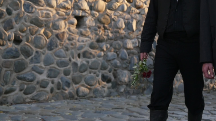 Two people dressed in black walk together down a cobblestone path while solemnly holding flowers. Slow motion waist height shot. Royalty-Free Stock Footage #1054074410