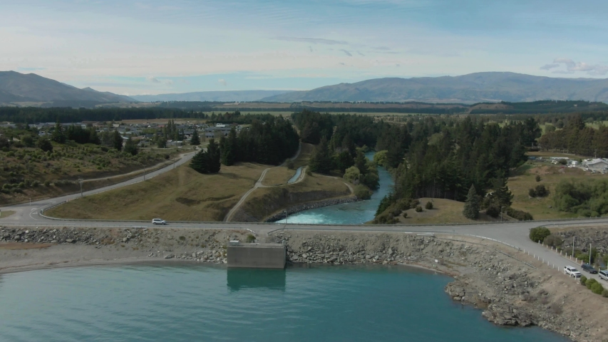 Areal footage above a lake dam wall with a road on it and a water power station behind it. Dam wall at lake Hawea in New Zealand. 4k video