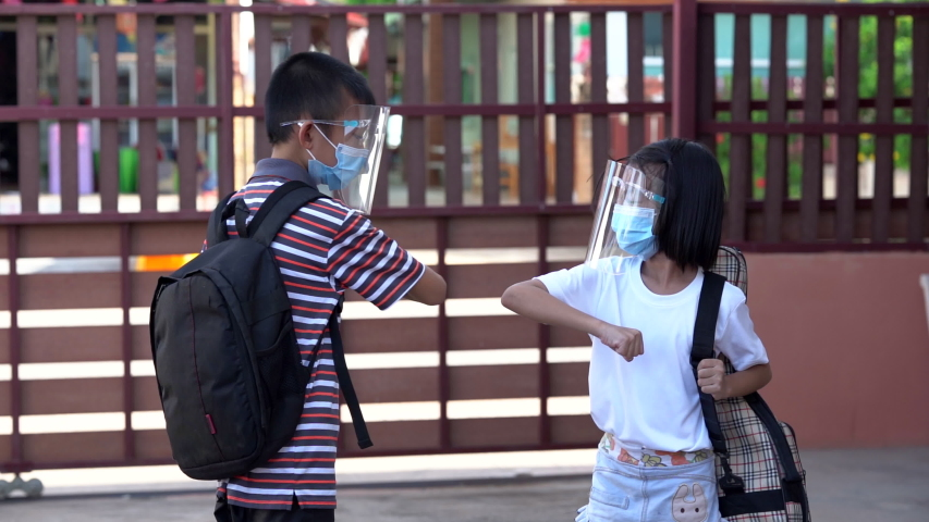 Covid-19 safety and social distancing concept, kids greeting elbow touch elbow before to classroom, Asian kid back to school of Thailand, Cute children smile under mask and face shield for protect. Royalty-Free Stock Footage #1054074488