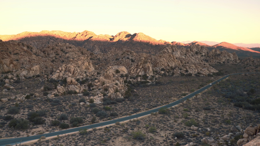 A car travelling on a road at dawn in the Joshua Tree National Park.